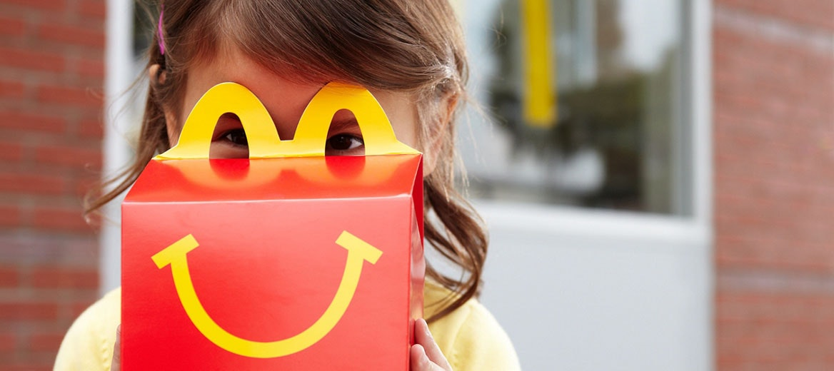 Little girl looking through a happy meal box